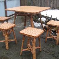 Кухонный квадратный плетеный стол и четыре квадратных плетеных стула.